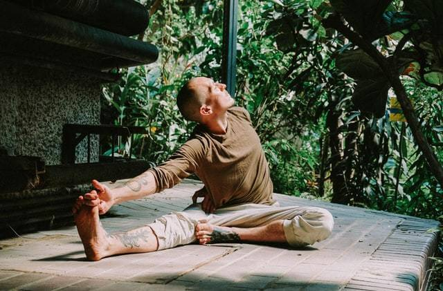 man wearing brown top and cream pants doing yoga pose stretch outdoors