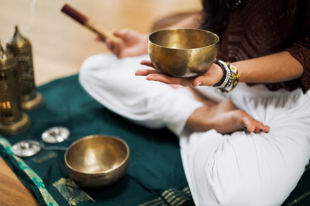 person sitting in a lotus position holding mallet in one hand and singing bowl in the other