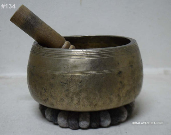 singing bowl with mallet inside placed on a gray felt cushion