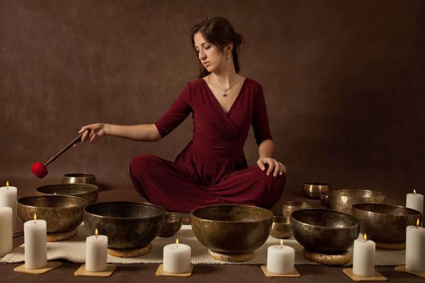 woman wearing red dress surrounded by singing bowls and white candles