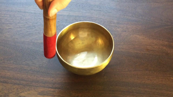 hand holding wooden mallet with red suede cover circling on a Shanti Bowl tiny singing bowl