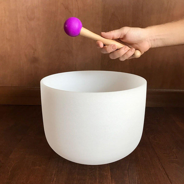 hand holding wooden mallet with purple ball jointed tip white crystal singing bowl underneath