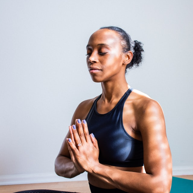 african woman hands in prayer pose near chest eyes closed