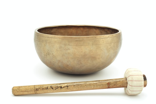 plain singing bowl wooden mallet cloth circle end white background
