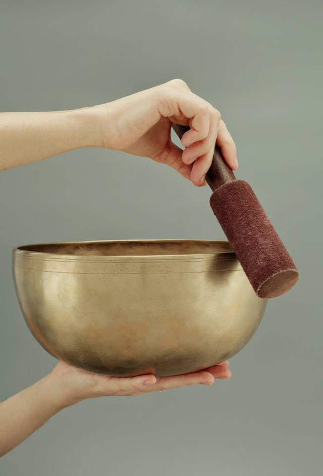 one hand holding singing bowl other hand holding mallet circling the rim
