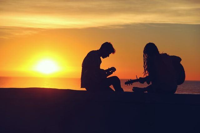 silhouette of two persons playing musical instrument sunset behind them