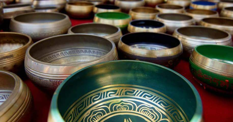 many pieces of singing bowls different colors spread on a red floor