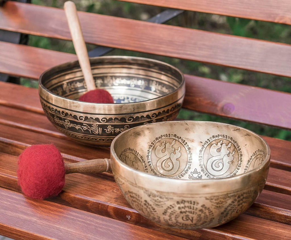 two gold singing bowls with elaborate design and writings inscription two mallets with red suede cover