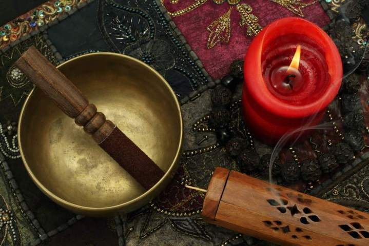 wooden mallet with suede cover placed inside a singing bowl