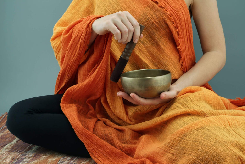 person with orange shawl over her body holding singing bowl and mallet