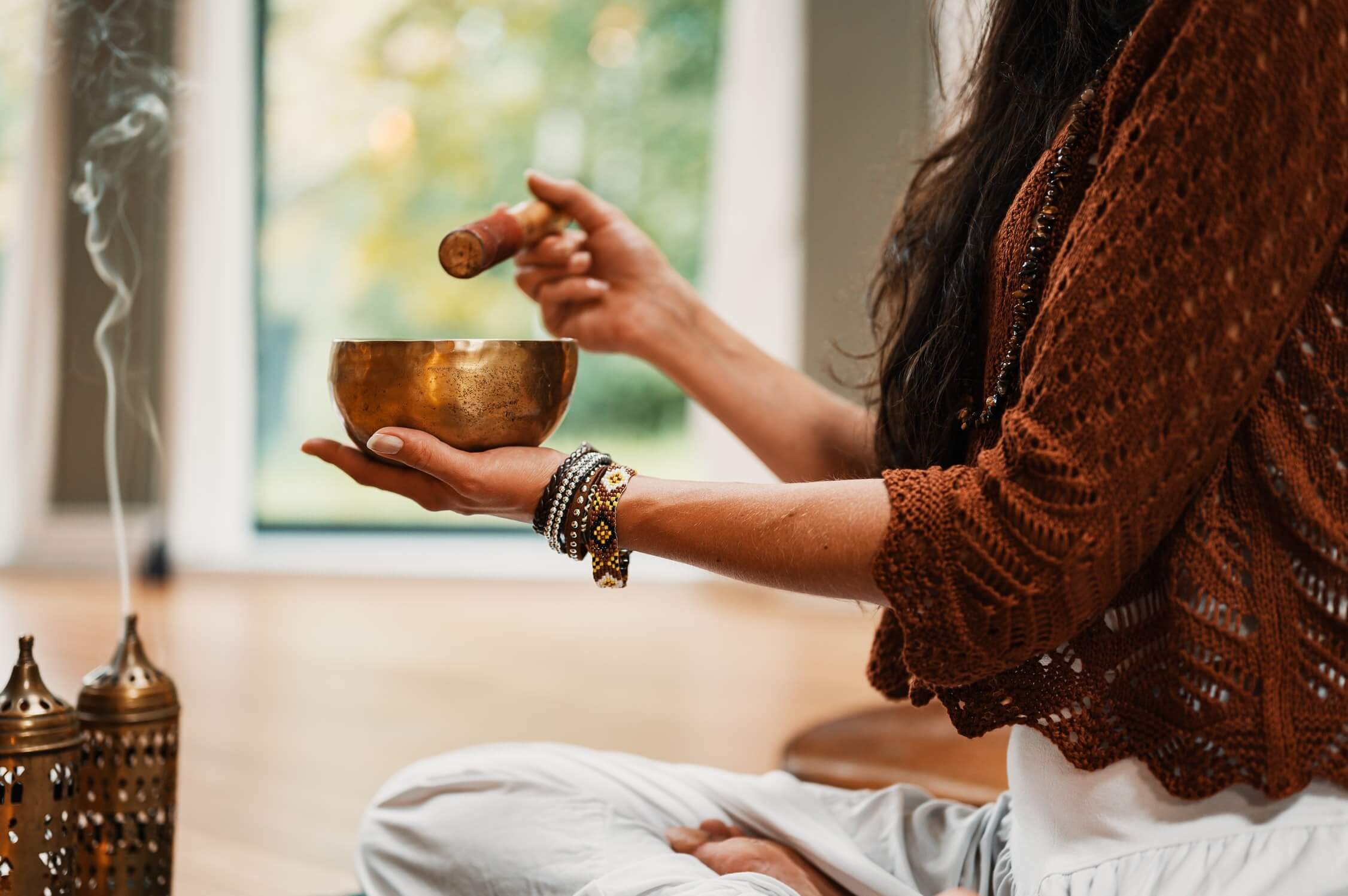 woman in brown outfit sitting in lotus position holding small singing ball and wooden mallet