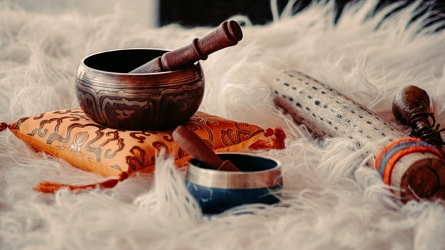 two singing bowls with etched design placed on a yellow pillow and fluffy white rug