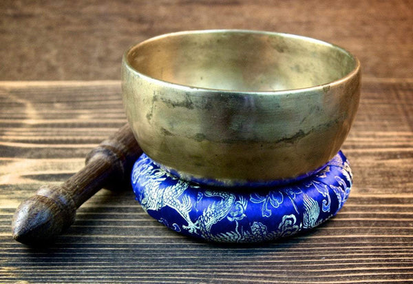 plain singing bowl placed on a blue dragon embroidered pillow