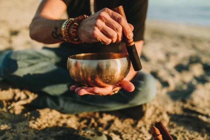 person sitting on a beach shore holding and playing singing bowl