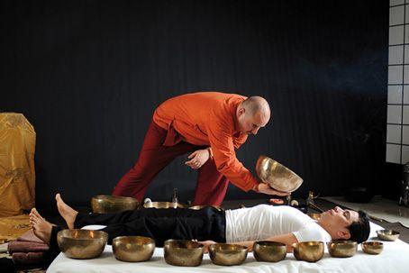man lying down surrounded by many singing bowls another man holding one bowl nearby