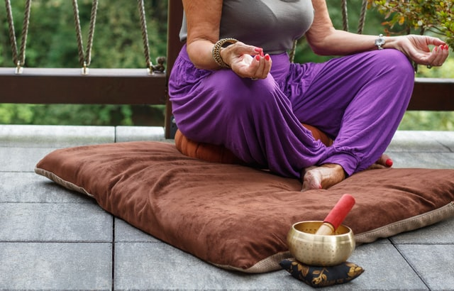 person wearing purple pants sitting in a lotus position on a brown pillow singing bowl and mallet nearby