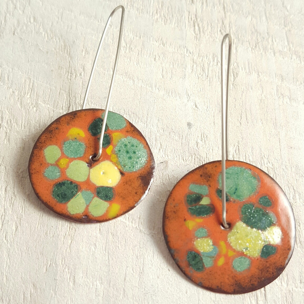 Orange enameled copper earrings with green accents.