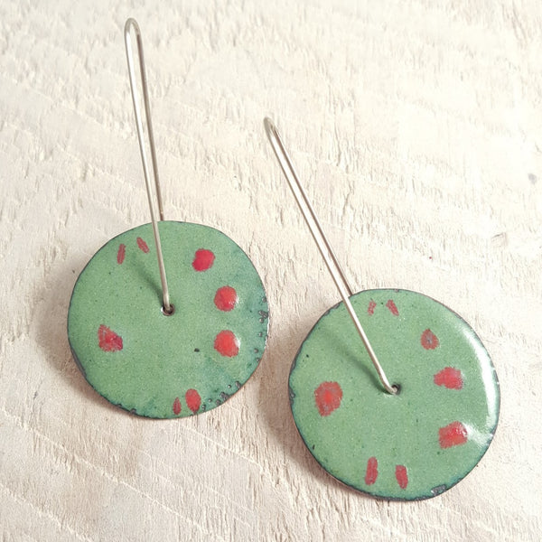 Green enameled copper earrings with red accents.