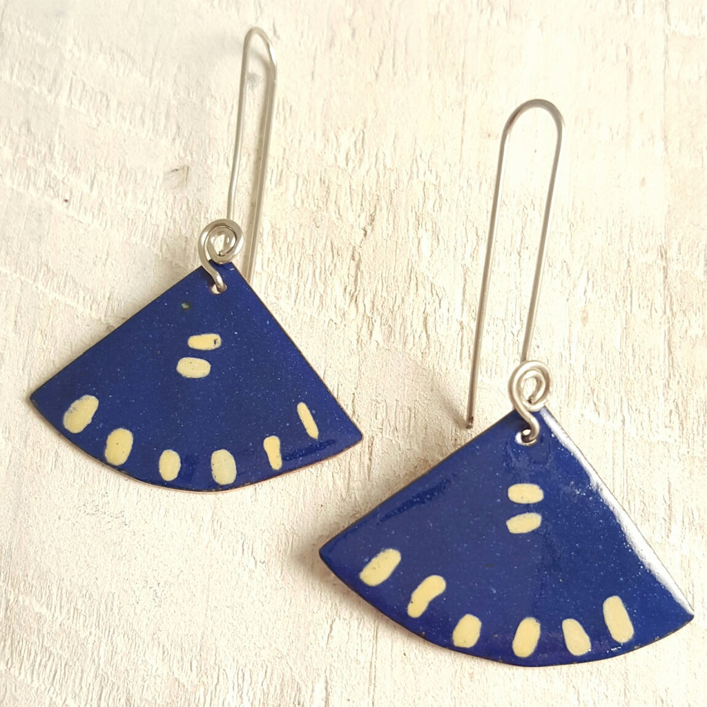 Dark blue enameled copper earring with cream accents.