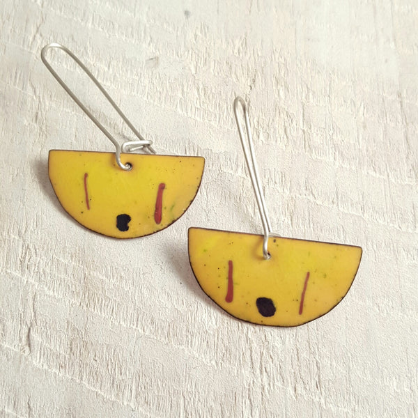 Yellow enameled copper earring with black and red accents.