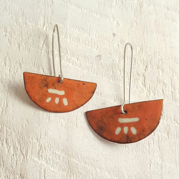 Orange enameled copper earrings with cream accents.