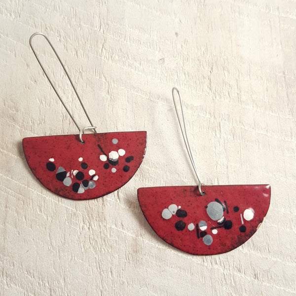 Dark red enameled copper earrings with black, grey, and white accents.