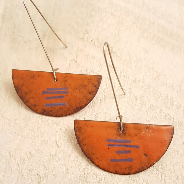 Orange enameled copper earrings with purple accents.
