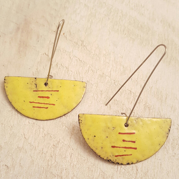Yellow enameled copper earring with red accents.