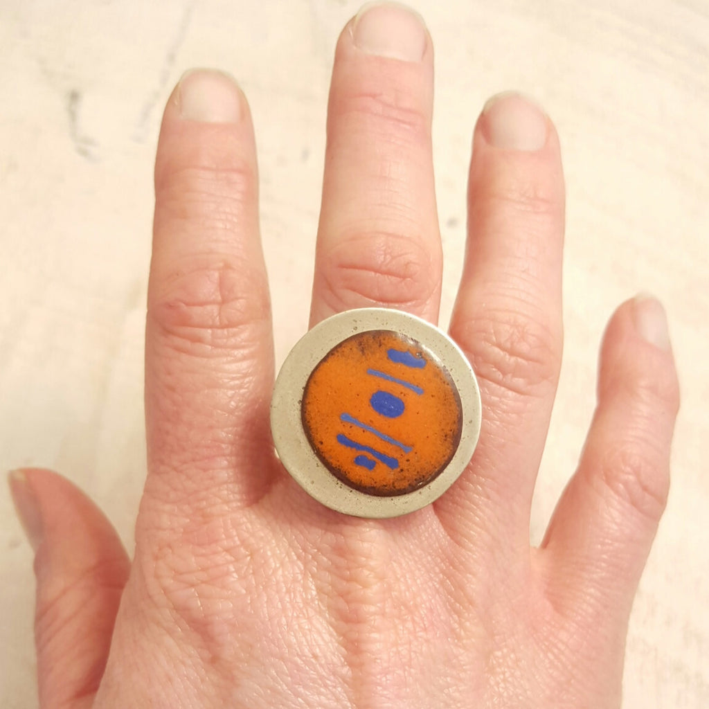 Orange enameled copper ring with blue accents.