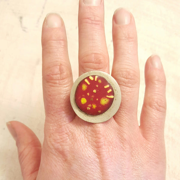 Red enameled copper ring with yellow accents.
