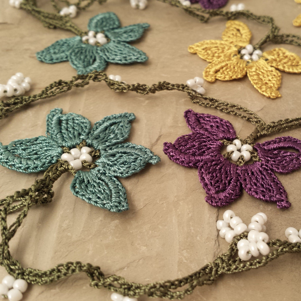 Purple, yellow, and teal flowers with green string.