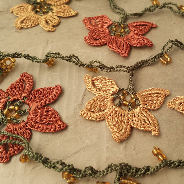 Gold and copper flowers with green string.