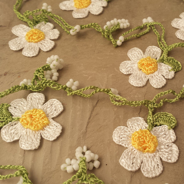 White daisy flowers with yellow center and light green string.