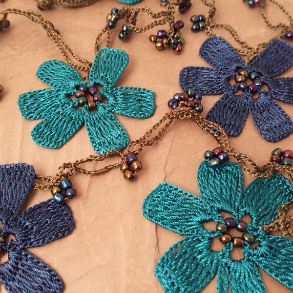Blue flowers in two shades with green string.