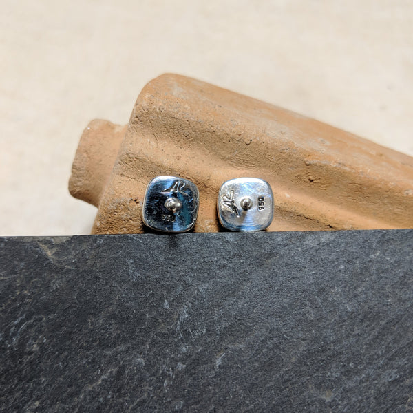 backs of stud with artist stamp and silver marker