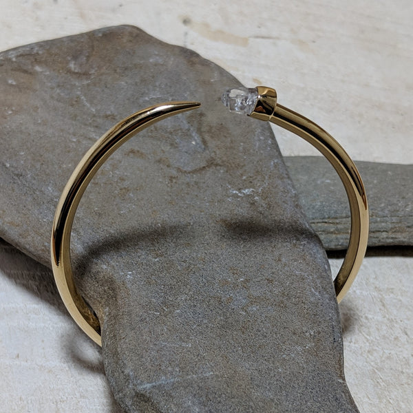 gold tusk bangle angled view with quartz