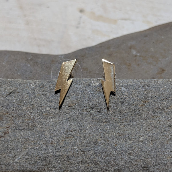 front of gold lightning bolt studs