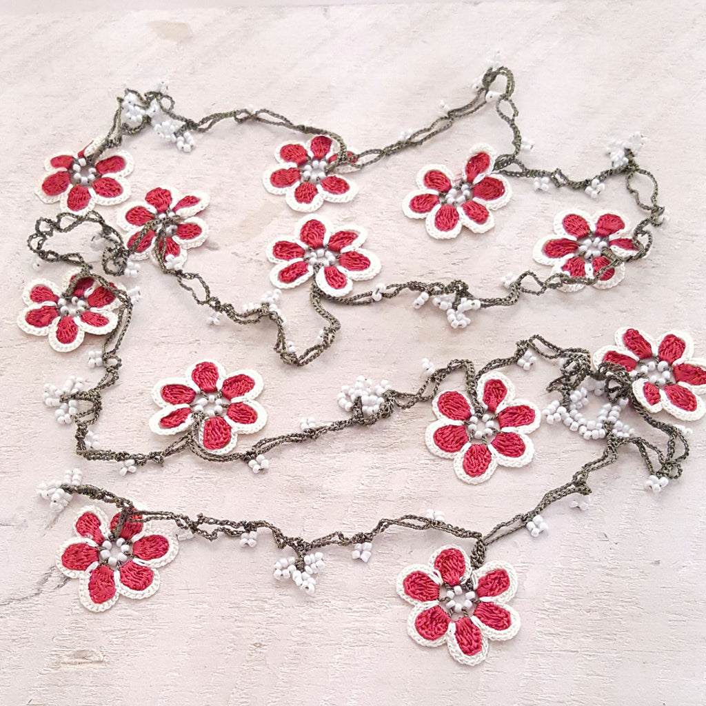 Red flowers with white borders and green string.