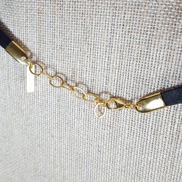 back of gold geometric necklace with black leather
