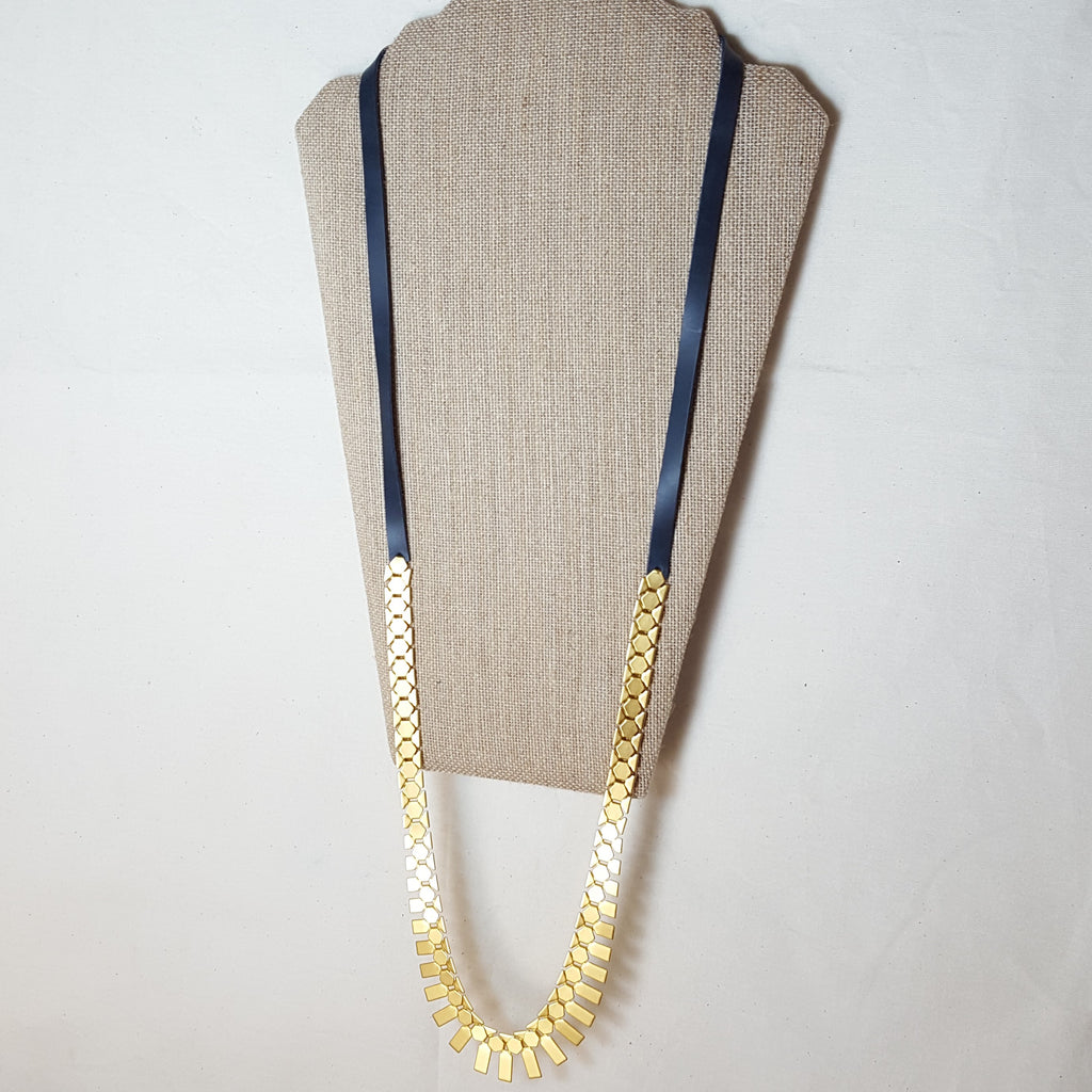 long gold geometric necklace with grey leather