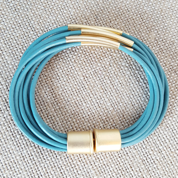 side view of gold tubes bracelet with turquoise leather