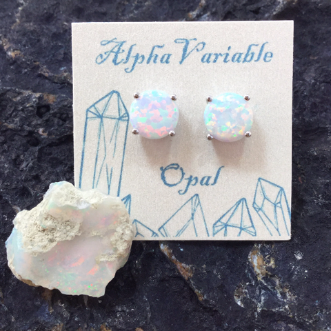 Sterling Silver Opal Earrings Ciruclar Studs on a card next to a raw Ethiopian Fire Opal