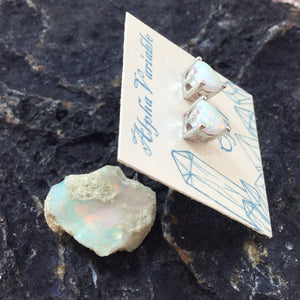Sterling Silver Opal Earrings Profile Heart Studs on a card next to a raw Ethiopian Fire Opal