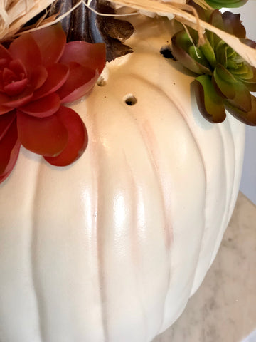 A white faux pumpkin with a brown spot and holes where faux succulents are placed.