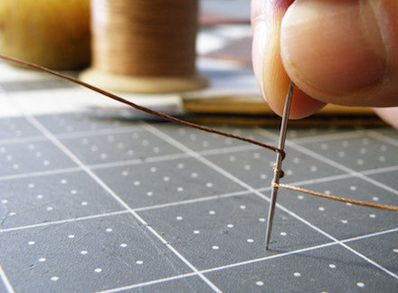 preparing the needle and thread for stitching leather