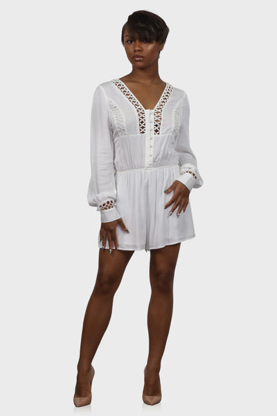 White long sleeve romper with button down front and lattice details on model front view