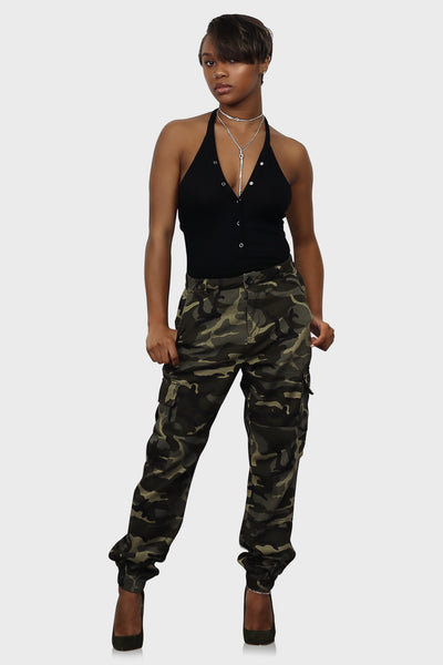 Olive camo joggers with side and back pockets, belt hoops, a zippered closure and elasticated ankle cuffs on model front view