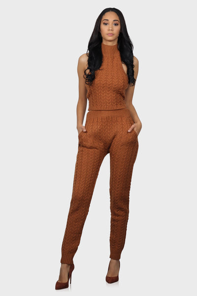 Cable knit pants rust color with side pockets, a ribbed waistline and ribbed ankle cuffs on model front view