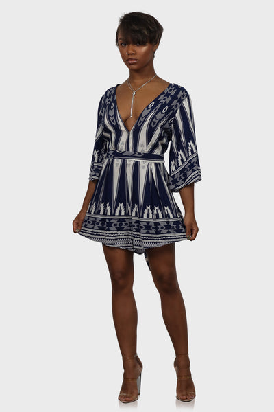 Navy blue romper tie front with low v neckline and cutout back on model front view
