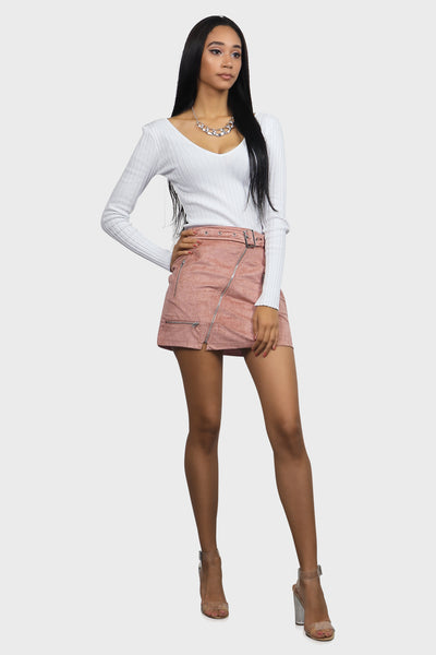 Pink mini skirt suede with zipper details and an attached grommet belt on model front view